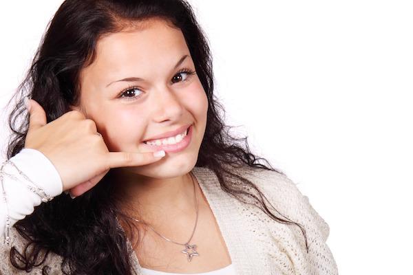笑顔で電話の真似をする女性